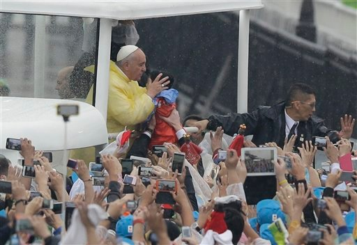Pope Francis kisses a child as he arrives at Rizal Park to celebrate his final Mass in Manila, Philippines, Sunday, Jan. 18, 2015. Millions filled Manila's main park and surrounding areas for Pope Francis' final Mass in the Philippines on Sunday, braving