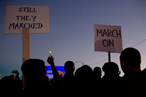 """Marchers hold up a """"March On"""" and """"Still They Marched"""" signs as they make their way towards the Edmund Pettus Bridge the Edmund Pettus Bridge in honor of Martin Luther King Jr., Sunday, Jan. 18, 2015, in Selma, Ala. Several clebraties such as Oprah Winfre"""