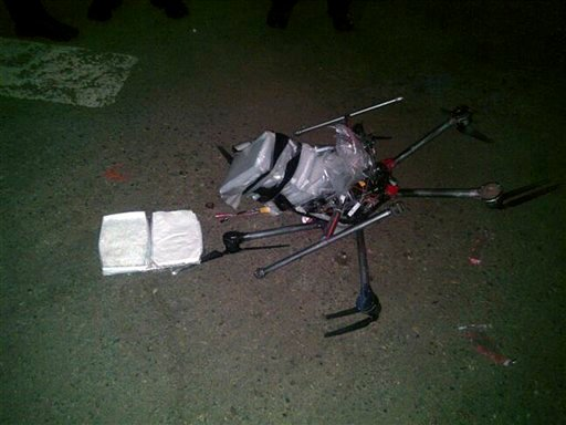 In this image released by the Tijuana Municipal Police on Wednesday Jan. 21, 2015, a drone loaded with packages containing methamphetamine lies on the ground after it crashed into a supermarket parking lot in the city of Tijuana on Tuesday Jan. 20, 2015.