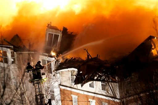 Firefighters stand on a ladder while hosing water onto an apartment complex, Wednesday, Jan. 21, 2015, in Edgewater, N.J. Authorities had not determined the cause of the fire. (AP Photo/Julio Cortez)