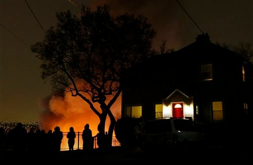 People look over the edge of a cliff at a large fire at an apartment complex, Wednesday, Jan. 21, 2015, in Edgewater, N.J. Authorities had not determined the cause of the fire. (AP Photo/Julio Cortez)