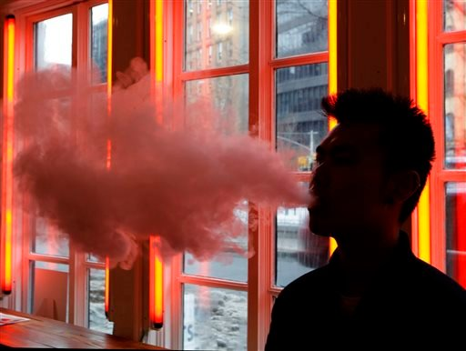 In this Feb. 20, 2014 file photo, a man exhales vapor from an e-cigarette in New York.