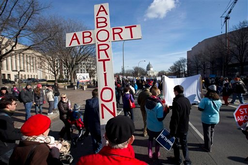 "Roy Rohn, 87, of Riverdale, Md., carries a cross that says ""abort abortion"" as anti-abortion demonstrators march toward the Supreme Court in Washington, Thursday, Jan. 22, 2015, during the annual March for Life on the National Mall. (AP)"
