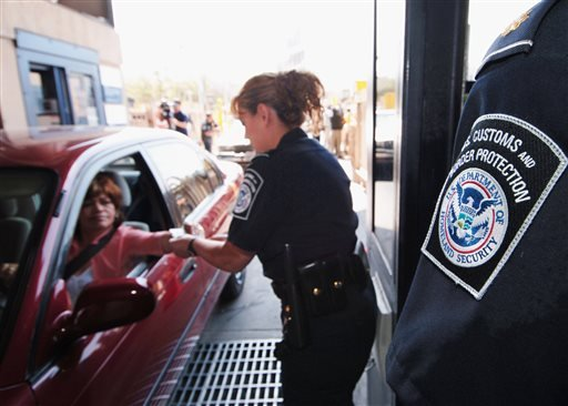 In this June 21, 2005, file photo, U.S. Customs and Border Protection Inspector Maria Arreola checks an electronic ID card at one of two new Secure Electronic Network for Travelers Rapid Inspection lanes at the San Ysidro Port of Entry in San Diego.