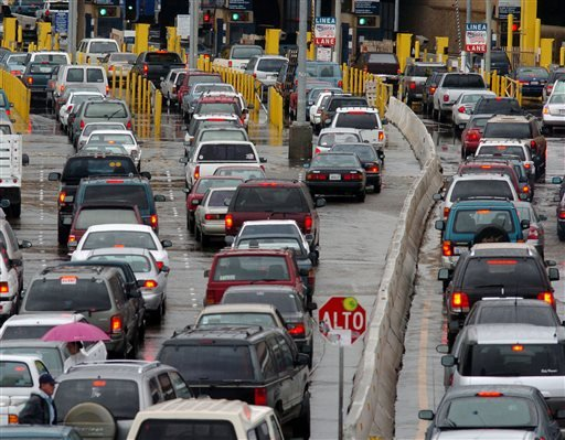 In this April 28, 2005, file photo, traffic jams the entry lanes into the United States from Tijuana, Mexico, in San Diego, including the Secure Electronic Network for Travelers Rapid Inspection lanes, at right of the concrete barrier.