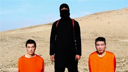 This file image taken from an online video released by the Islamic State group's al-Furqan media arm on Tuesday, Jan. 20, 2015, purports to show the group threatening to kill two Japanese hostages that the militants identify as Kenji Goto Jogo, left, and