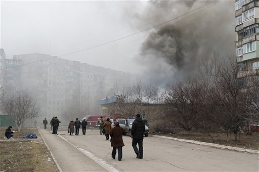 Residents pass by burning houses, a dead body in the background, in Mariupol, Ukraine, Saturday, Jan. 24, 2015. A crowded open-air market in Ukraine's strategically important coastal city of Mariupol came under rocket fire Saturday morning, killing at lea