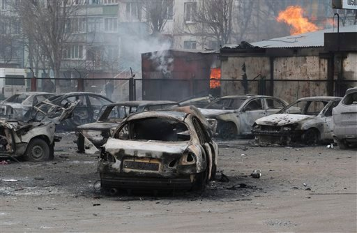 Burned cars on a destroyed parking site in a residential area in Mariupol, Ukraine, Saturday, Jan. 24, 2015. A crowded open-air market in Ukraine's strategically important coastal city of Mariupol came under rocket fire Saturday morning, killing at least