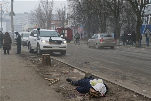 A dead body lays on the ground in a residential area in Mariupol, Ukraine, Saturday, Jan. 24, 2015. A crowded open-air market in Ukraine's strategically important coastal city of Mariupol came under rocket fire Saturday morning, killing at least 10 people