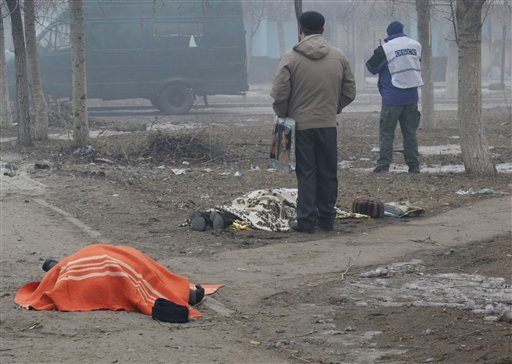 Two dead bodies lay on the ground in a residential area in Mariupol, Ukraine, OSCE members in the background, Saturday, Jan. 24, 2015. A crowded open-air market in Ukraine's strategically important coastal city of Mariupol came under rocket fire Saturday