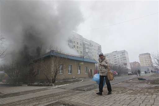 A woman resident passes by a burning house in Mariupol, Ukraine, Saturday, Jan. 24, 2015. A crowded open-air market in Ukraine's strategically important coastal city of Mariupol came under rocket fire Saturday morning, killing at least 10 people, regional