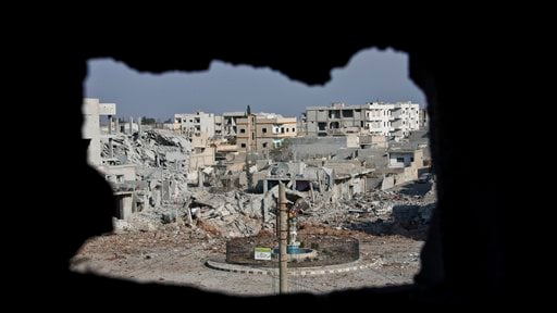 This Nov. 20, 2014 file photo shows an area controlled by the Islamic State group, past the Qada Azadi roundabout, foreground, in Kobani, Syria. Kurdish fighters backed by intense U.S.-led airstrikes pushed the Islamic State group almost entirely out of