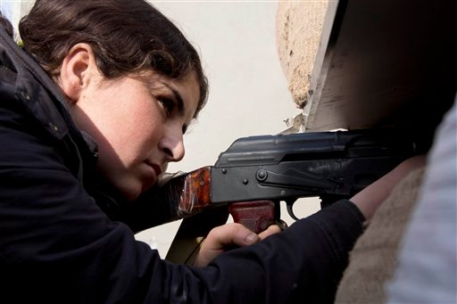 In this Wednesday, Nov. 19, 2014 photo, a female Kurdish fighter takes aim in Kobani, Syria. Kurdish fighters backed by intense U.S.-led airstrikes pushed the Islamic State group almost entirely out of the Syrian town of Kobani on Monday, Jan. 26, 2015, m