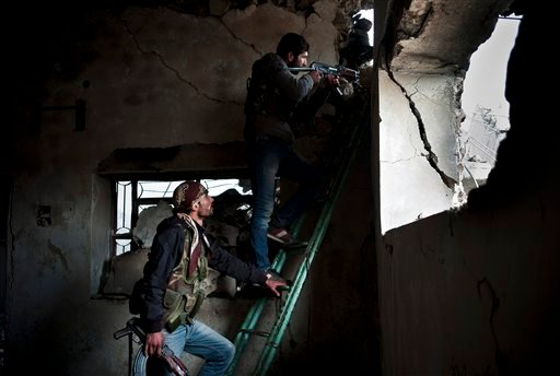 In this Nov. 1, 2014 file photo, Kurdish fighters take up different positions to lure Islamic State group militants to give their location in Kobani, Syria. Kurdish fighters backed by intense U.S.-led airstrikes pushed the Islamic State group almost entir