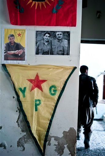 In this Nov. 2, 2014 photo, pictures adorn the walls of a position held by Kurdish popular protection (YPG) and women's defense (YPJ) units of fighters who have been lost in the battles against the Islamic State group in Kobani, Syria. Kurdish fighters ba