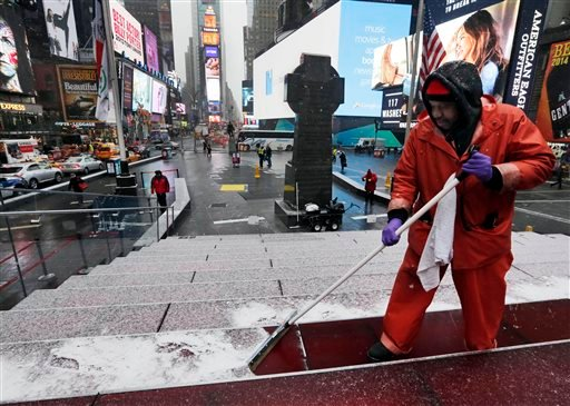 Francisco Mathurine, of the Times Square Alliance, clears snow from the steps in Father Duffy Square in New York, Monday, Jan. 26, 2015. Officials cautioned Northeast residents to not be misled by a relatively smooth Monday morning commute, and pressed th