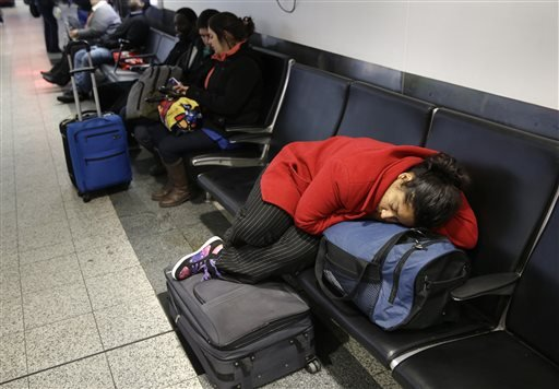 A woman sleeps on top of her luggage at LaGuardia Airport in New York, Monday, Jan. 26, 2015. Airlines canceled thousands of flights into and out of East Coast airports as a major snowstorm packing up to 3 feet of snow barrels down on the region. (AP Phot