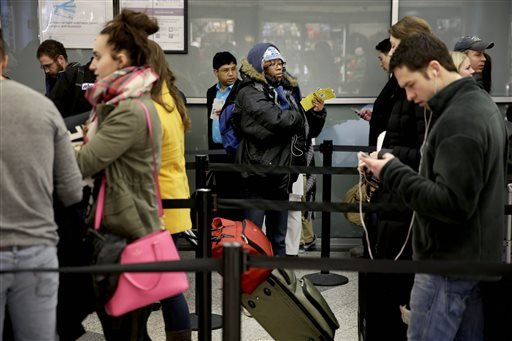 Air travelers wait to to board a flight at LaGuardia Airport in New York, Monday, Jan. 26, 2015. (AP)