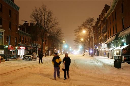 People walk down the middle of a street past entrances to the subway, left and right, in the Park Slope neighborhood in the Brooklyn borough of New York, early Tuesday, Jan. 27, 2015. The city shut down the subway system in advance of the storm. Tens of m