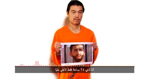 This still image taken from a video posted on YouTube by jihadists on Tuesday, Jan. 27, 2015, shows a still photo of Japanese journalist Kenji Goto holding what appears to be a photo of Jordanian pilot 1st Lt. Mu'ath al-Kaseasbeh. Both are being held host