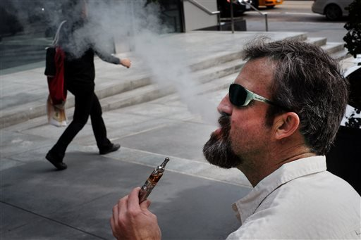 Paul Frohman smokes an electronic cigarette outside an office building in downtown Los Angeles on Wednesday, Jan. 28, 2015. (AP)
