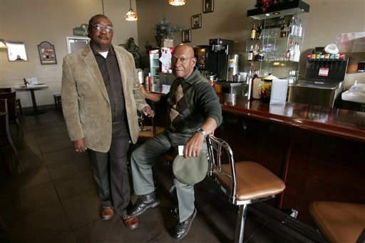 """FILE - In this March 5, 2009, file photo, the Rev. W. T. """"Dub"""" Massey, right, and Willie McLeod, left, pose at the counter where they were among the """"Friendship Nine"""" who were jailed during 1960s civil rights """"sit-ins."""" (AP)"""