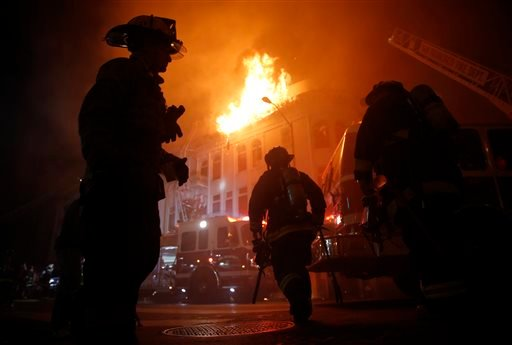 San Francisco Fire Department members fight a four-alarm fire at 22nd and Mission Street in San Francisco, Calif., on Wednesday, Jan. 28, 2015. (AP Photo/San Francisco Chronicle, Scott Strazzante)