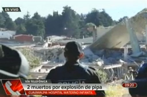 In this video image taken from Milenio TV via APTN, police look at the scene where a gas tank truck exploded outside a maternity and children's hospital in Mexico City, Thursday, Jan. 29, 2015. (AP Photo/Milenio TV via APTN)