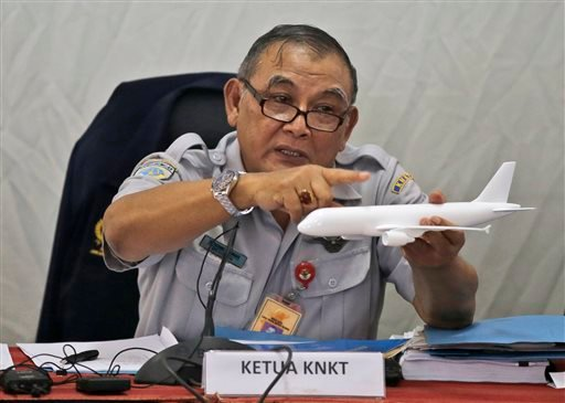 Indonesian NTS Committee chief Tatang Kurniadi speaks with a model plane of AirAsia Flight 8501 that crashed into the Java Sea on Dec. 28 last year during a press conference in Jakarta, Indonesia Jan. 29, 2015. (AP Photo/Dita Alangkara)