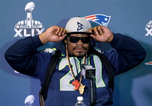 Seattle Seahawks' Marshawn Lynch adjusts his cap during an interview for NFL Super Bowl XLIX football game, Thursday, Jan. 29, 2015, in Phoenix. (AP)