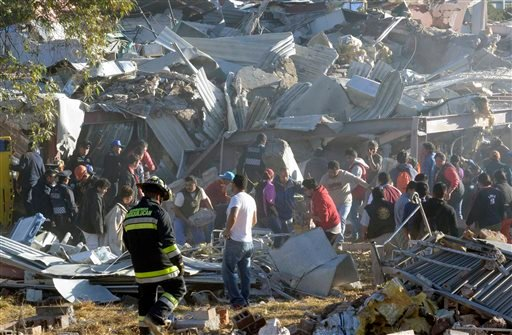 Rescue workers comb through the rubble of a children's hospital after a gas truck exploded, in Cuajimalpa on the outskirts of Mexico City, Thursday, Jan. 29, 2015.