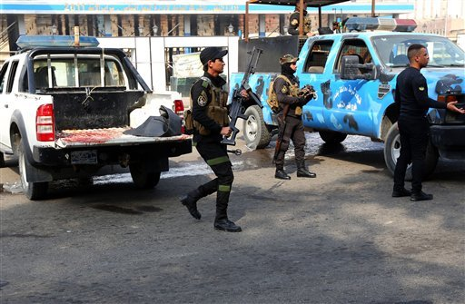Security forces inspect the site of a twin bombing at a crowded market in Baghdad Iraq, Friday, Jan. 30, 2015. Police officials say the Friday morning attack started with a bomb exploding near carts selling used clothes in the city's central Bab al-Sharqi