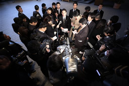 Japanese Foreign Minister Fumio Kishida, center top, surrounded by journalists is asked on Japanese journalist Kenji Goto taken hostage by the Islamic State group, at the prime minister's official residence in Tokyo, Friday, Jan. 30, 2015. (AP Photo/Eugen