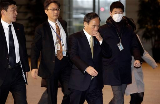 Japan's government spokesman Chief Cabinet Secretary Yoshihide Suga, center, arrives at the prime minister's official residence in Tokyo, Friday, Jan. 30, 2015. The father of a Jordanian fighter pilot and the wife of a Japanese journalist held by the Isla