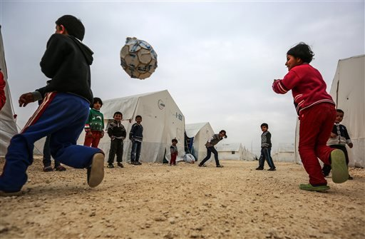 Syrian refugee children who fled violence in Syrian city of Ayn al-Arab or Kobani play outside their tent in Turkey's newly set-up camp in the border town of Suruc, Turkey, Friday, Jan. 30, 2015. The 35,000 people capacity camp is the biggest refugee camp