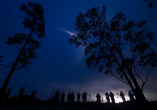 This photo taken with a long exposure provided by NASA, spectators watch as a Delta 2 rocket carrying the Soil Moisture Active Passive, SMAP, satellite launches early Saturday, Jan. 31, 2015 from Vandenberg Air Force Base, Calif. The launch is a three-yea