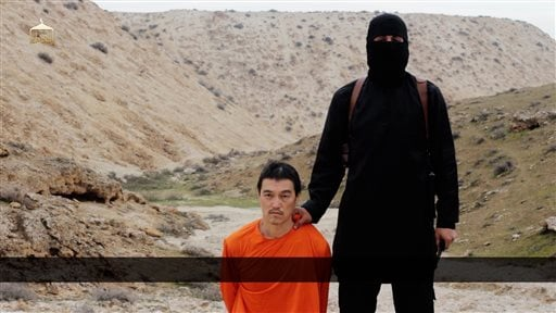 This image made from a video released by Islamic State militants on Saturday, Jan. 31, 2015, purports to show a militant standing next to Japanese journalist Kenji Goto before his beheading by the militant group.