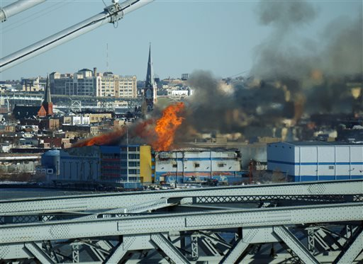 Seen from the Williamsburg Bridge, a fire burns at a warehouse in the Brooklyn borough of New York on Saturday, Jan. 31, 2015. More than 200 firefighters battled the blaze in frigid temperatures and strong winds. The building contained offices, storage an
