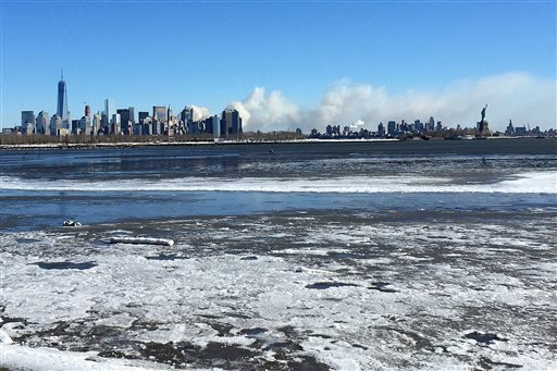 Smoke rises behind the New York City skyline, Saturday, Jan. 31, 2015, seen from Jersey City, N.J. Firefighters battled a multi-alarm blaze inside a Brooklyn storage facility that was fed by the paper inside. No injuries were immediately reported. More th