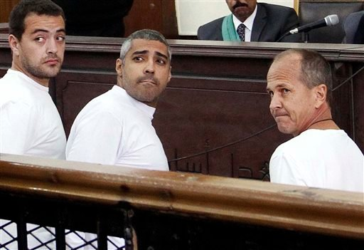 In this Monday, March 31, 2014 file photo, Al-Jazeera English producer Baher Mohamed, left, Canadian-Egyptian acting Cairo bureau chief Mohammed Fahmy, center, and correspondent Peter Greste, right, appear in court along with several other defendants dur