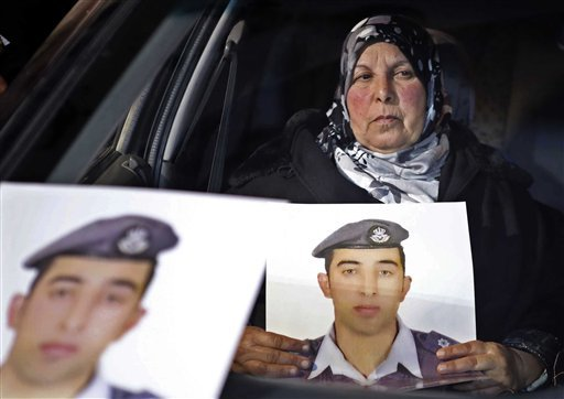 In this Tuesday, Jan. 27, 2015 file photo, the mother of Jordanian pilot Lt. Mu'ath al-Kaseasbeh holds a picture of her son, who is held by Islamic State group militants, in a car during a sit-in in front of the cabinet offices in Amman, Jordan. An online