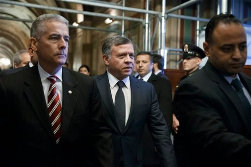 King Abdullah of Jordan , center, is hurried into a meeting with leaders of the Senate Foreign Relations Committee at the Capitol in Washington, Tuesday, Feb. 3, 2015. (AP)