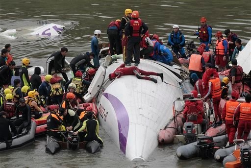 Emergency personnel try to extract passengers from a commercial plane after it crashed in Taipei, Taiwan, Wednesday, Feb. 4, 2015. (AP Photo/Wally Santana)