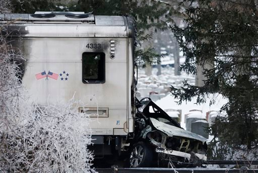 A sports utility vehicle remains crushed and burned at the front of a Metro-North train, Wednesday, Feb. 4, 2015, in Valhalla, N.Y. (AP Photo/Mark Lennihan)