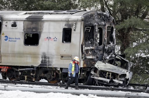 A man wearing a Federal Railroad Administration vest looks over the wreckage of a a Metro-North Railroad train and an SUV in Valhalla, N.Y. Feb. 4, 2015. (AP Photo/Seth Wenig)