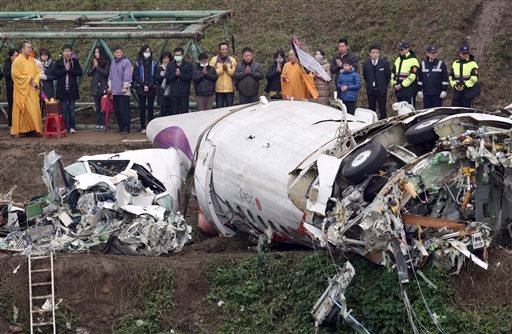 Relatives of the victims in a commercial plane crash pray over the wreckage along the river bank in Taipei, Taiwan, Thursday, Feb. 5, 2015. (AP Photo)