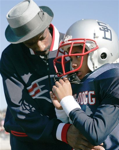 In this Feb. 5, 2005 file photo, Rap artist and actor Snoop Dogg, left, talks to his son Cordell Broadus, 7, a member of the the Snoop All-Stars youth football team.