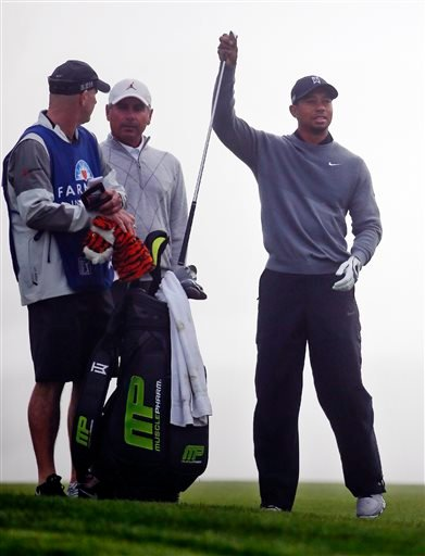 Tiger Woods pulls a club from the bag as his caddie Joe LaCava, left, talks with Fred Couples, who walked the course with Woods, during the pro-am at the Farmer Insurance Open golf tournament at Torrey Pines, Wednesday, Feb. 4, 2015, in San Diego.