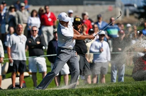 Tiger Woods hits from the green side bunker on the par five 14th hole of the north course at Torrey Pines during the first round of the Farmers Insurance Open.