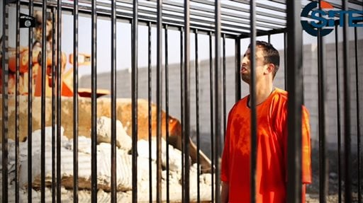 This still image made from video released by Islamic State group militants and posted on the website of the SITE Intelligence Group in this Tuesday, Feb. 3, 2015 file photo, purportedly shows Jordanian pilot Lt. Muath al-Kaseasbeh standing in a cage just